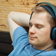 This is a photograph of laying young man listening music — Stock Photo #5741743