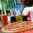 Closeup of a table with pizza and cook hat — Stockfoto