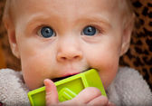 Baby holding a green block facing camera — Foto de Stock