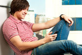 Smiling trendy young guy typing a message on mobile phone — ストック写真