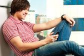 Souriant tendance jeune mec tape un message sur téléphone mobile — Photo