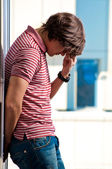 Depressed young man standing against window in the background — Stockfoto