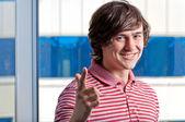 Junger mann mit einem schild sie gegen das fenster gestikulieren — Stockfoto