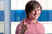 Young guy gesturing with a YOU sign against the window — Stockfoto