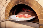 Baked pizza by the fire in oven — Stock Photo