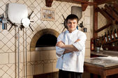 A young chef standing next to oven — Foto de Stock