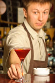 A barman holding the glass with cocktail — Stock Photo