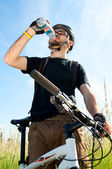 Closeup of a young biker drinking water — Stock Photo