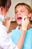 Young dentist giving a treatment to her patient — Stock Photo
