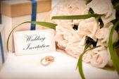 Svatební pozvánky s kroužky, dárky a růže — Stock fotografie