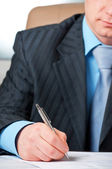 Businessman with pen signing contract — Stockfoto