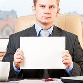 Young businessman holding blank paper — Stock Photo