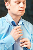 Young businessman tying a tie — Stock Photo