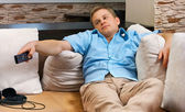 Man lying on sofa watching TV at home. — Stock Photo