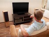 Mężczyzna leżał na kanapie oglądając tv w domu. — Zdjęcie stockowe