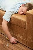 Wiskey bir şişe ile kanepede uyuyan genç bir adam — Stok fotoğraf