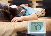 Jovem com despertador em primeiro plano a dormir — Foto Stock