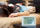 çalar saat yönü ön planda olan genç adam uyuyan — Stok fotoğraf