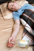 A young man sleeping on the couch with a bottle of wiskey — Stock Photo