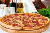 Closeup of a pizza with salami and mushrooms — Stock Photo