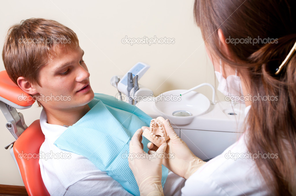 Dentist showing dental molds to her patient — Stock Photo #5741243
