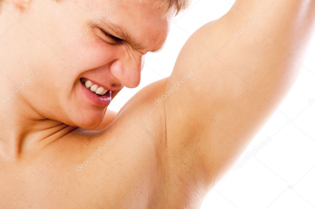 Closeup of young man sniffing his armpit isolated on white background  Stock Photo #5741516