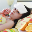 Stock Photo: Sick young girl with a thermometer in bed