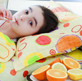 Sick little girl with a thermometer in bed — Stock Photo