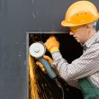 Worker in orange helmet with angle grinder. Half length portrait — Stock Photo