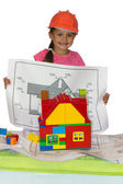 Cute girl in orange helmet with house project — Stock Photo