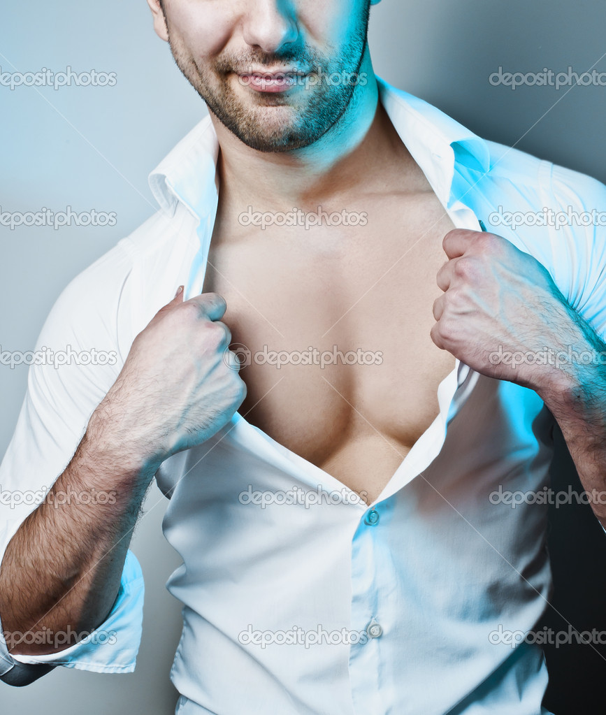 Studio shot of a young sexy man unbuttoning his white shirt under blue spotlight — Stock Photo #5668568