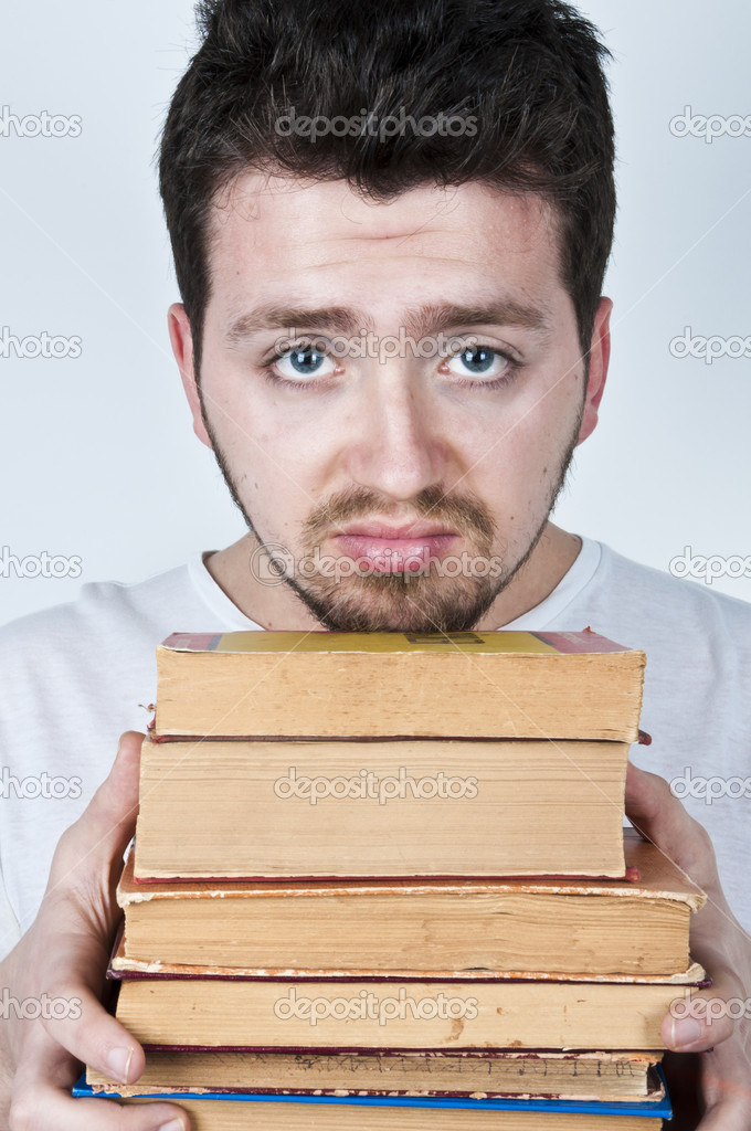 Young man holding a stack of old books looking bored and unhappy — Stock Photo #5720153