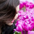 Pretty girl smelling tulips — Stock Photo
