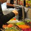 Man preparing salad on the buffet - Stock Photo
