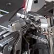 Thread in needle of sewing machine closeup - Stock Photo