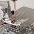 Stock Photo: Thread in needle of sewing machine closeup