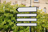 4 white guide sign in town — Stock Photo