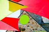 Colour umbrella and stone wall — Stock Photo