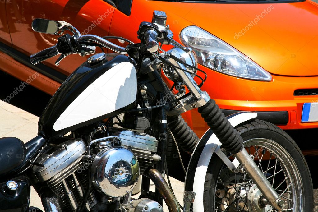 Brutal bike and orange lady's car — Stock Photo #5720045