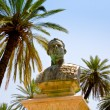 Old bronze bust under palm trees - Foto Stock