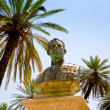 Old bronze bust under palm trees - Foto de Stock