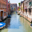 Canal, boats and bridge in Venice - Stock Photo