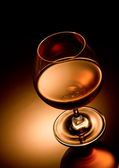 Glass of brandy over gold background — Stock Photo