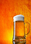 Glass of beer close-up with froth over orange background — Stock Photo