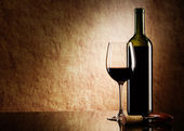 Green bottle with red wine and glass and cork with a corkscrew on a old sto — Stock Photo