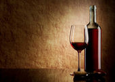 White bottle with red wine and glass and cork with a corkscrew on a old sto — Stock Photo