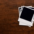 Empty instant photos on wooden table background — Stock Photo