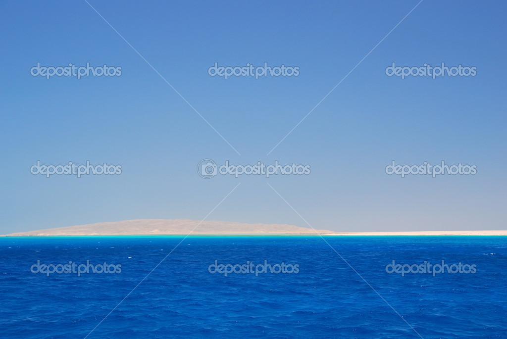 Blue sea and white sand beach on the horizon an island with  Stock Photo #5983916