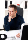 Young man thinking in front of his computer — Stock Photo