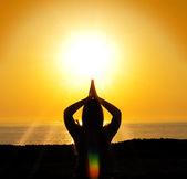 Woman yoga silhouette in the sun — Stock Photo